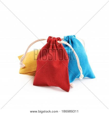 Pile of cloth gift bags with the lace stringing, composition isolated over the white background