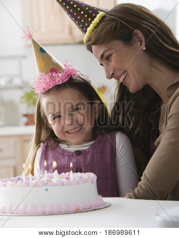 Caucasian mother and daughter with birthday cake