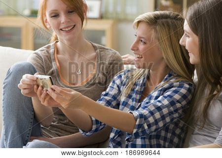 Caucasian teenage girls looking at photographs