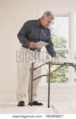 Caucasian man holding digital tablet looking at blueprint