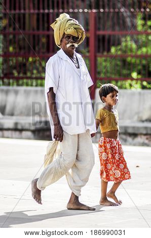 Ranakpur India september 11 2010: Old indian man with a girl in turban and traditional clothes walking on a street.