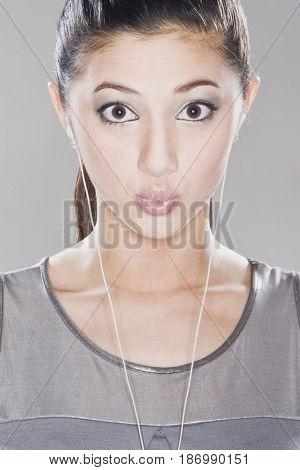 Surprised mixed race woman listening to headphones