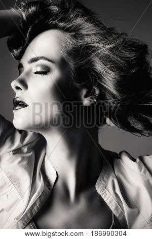 Black-and-white beauty portrait. Make-up, cosmetics concept. Exciting young woman with beautiful curly hair posing in a motion.