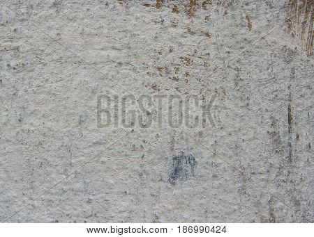 The concrete wall is covered with a gray facing filler. On the old wall there are scratches and rubs of various sizes.