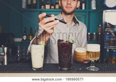 Alcohol cocktails. Professional bartender makes refreshing drinks. Selective focus on glasses