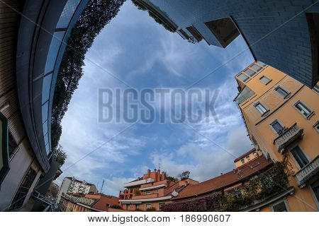 Milan (Lombardy italy): old typical residential buildings along via Piero della Francesca with dramatic sky. Fisheye lens.