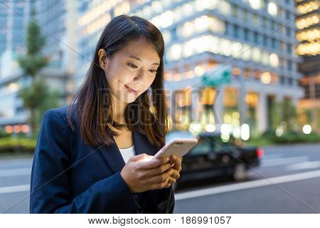 Businesswoman sending sms on mobile phone in Tokyo city at night
