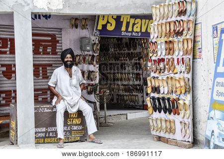 Amritsar India september 4 2010: Indian sikh in his shop selling shoes in Amritsar in India.