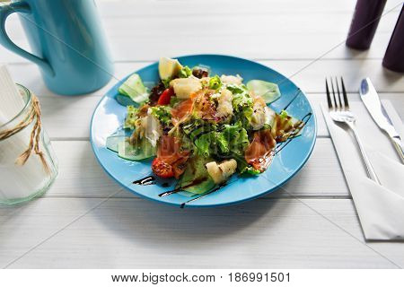 Restaurant healthy food, seafood salad on wood. Salmon and cod fish salad with vegetables and lettuce on blue plate.