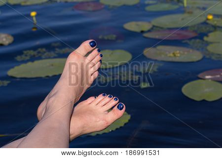 Female feet and a pond with water lilies. Relaxation