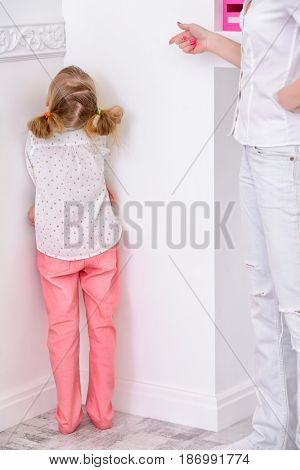 Mother scolds her daughter, puts her in a corner. Family concept, parenting.