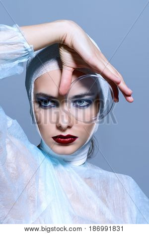 Close-up portrait of an attractive young woman in bandages holding a Petri dish. Beauty, fashion and medicine, plastic surgery. Studio shot.