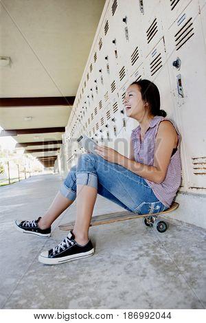 Chinese teenager on skateboard using digital tablet