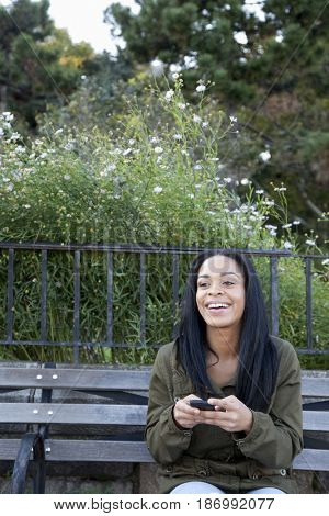 African American woman using cell phone on park bench
