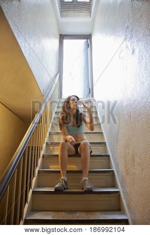 Caucasian woman drinking water on stairs after exercise