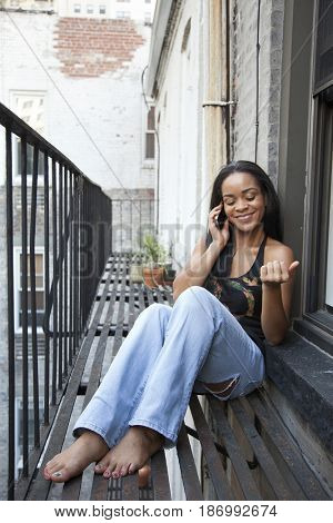 African American woman using cell phone on fire escape