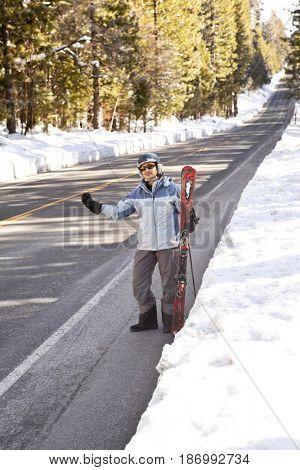 Hispanic man with skis hitchhiking