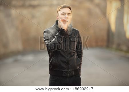 Handsome young man smoking weed outdoors