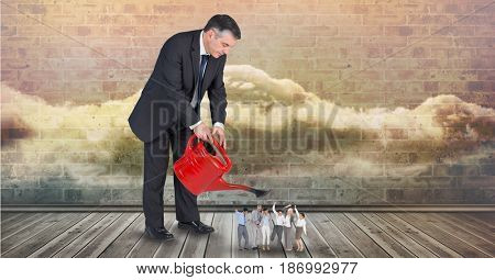 Digital composite of Digital composite image of businessman pouring water on employees from watering can