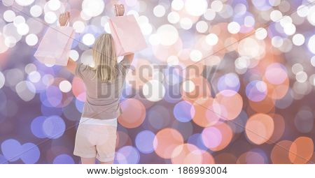 Digital composite of Happy female with shopping bags over bokeh