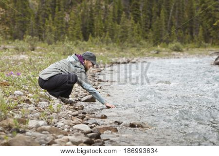Caucasian woman reaching into stream