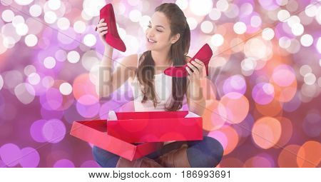 Digital composite of Happy woman looking at new red shoes over bokeh