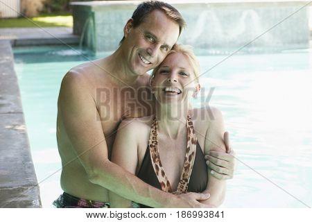 Caucasian couple hugging in pool