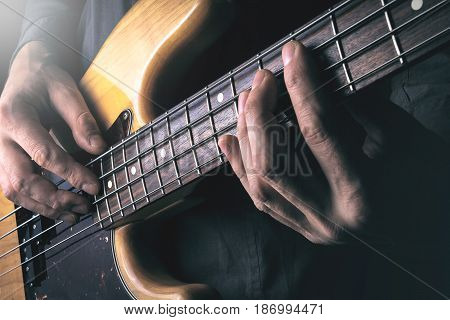 Live rock music background, electric bass guitar over bright blurred stage lights, close up, soft selective focus