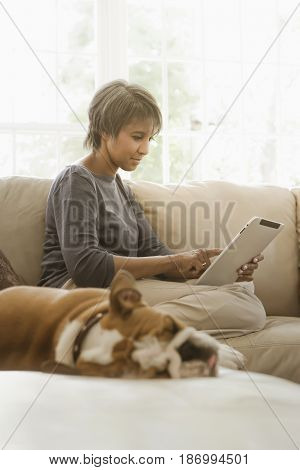 Native American woman using digital tablet on sofa