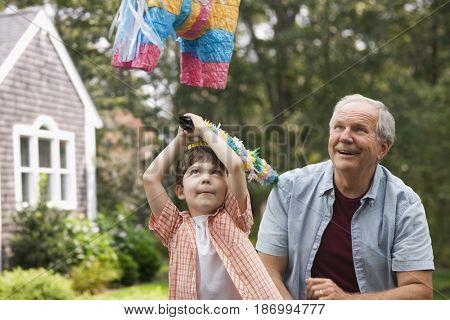 Caucasian man watching grandson hit pi_ata