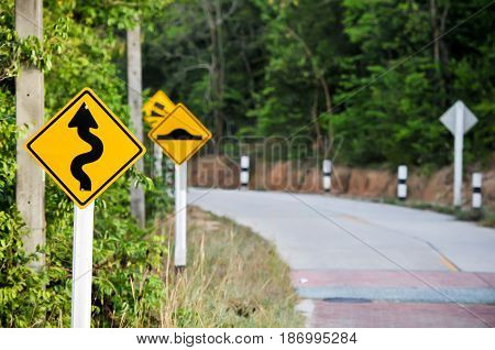 Traffic alerts downhill slope. Reduce speed and use a lower gear, Curvy road sign to the mountain in rural area