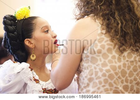 Hispanic mother putting lipstick on daughter