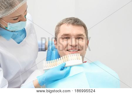 Dentist checking and selecting color of man's teeth