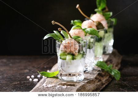 Verrines appetizer with salmon pate, red caviar, cucumber, cream cheese, herbs, capers in glasses served with pink salt and basil on wooden serving board over brown texture background.