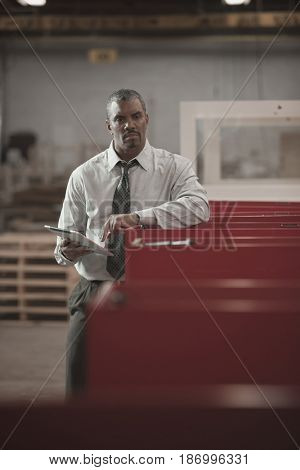 Black businessman using digital tablet in warehouse