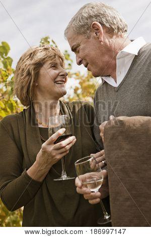 Caucasian couple drinking wine in vineyard