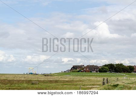 grasslands with cottages in the background cloudy sky
