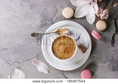 White cup of black coffee, served on white saucer with macaroons biscuits, spoon and magnolia flower blossom branch over gray texture background. Flat lay, space