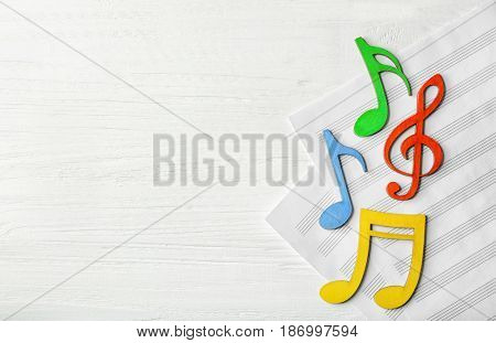 Colourful musical notes lying on music sheets on white wooden background