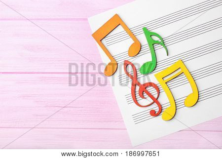 Colourful musical notes lying on music sheet on pink wooden background
