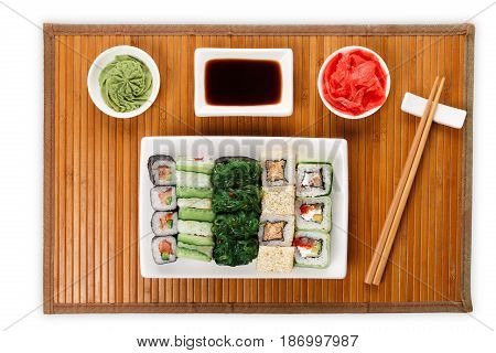 Japanese food restaurant delivery - sushi maki, unagi and roll platter set on mat isolated on white background, above view