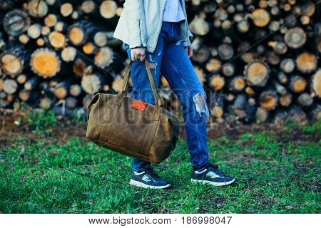 The young girl with a leather bag at a wall from logs. Rear view