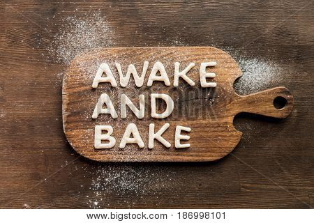 Top View Of Edible Lettering Awake And Bake Made From Dough On Wooden Cutting Board, Baking Cookies
