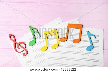 Colourful musical notes lying on music sheets on pink wooden background