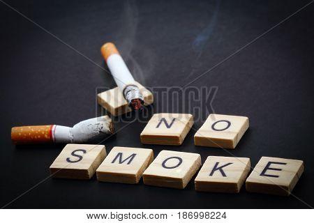 No smoke wording with cigarette on dark background.