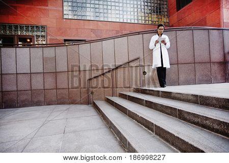 Doctor using digital tablet outdoors