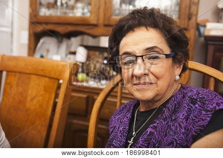 Senior Hispanic woman at dinner table