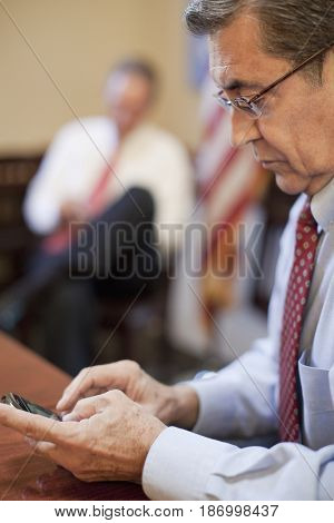 Hispanic businessman using cell phone