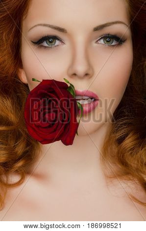 Red rose in the teeth of woman with red hair