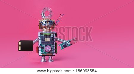 Cyber safety data storage concept. System administrator robot toy with usb flash stick and memory card on red background. Copy space macro view photo